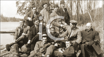 Royalty Free Photo of a Group of Men Sitting on a Riverbank