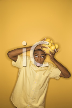 Royalty Free Photo of a Man Dropping a Bowl of Lemons He is Balancing on His Head