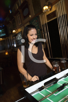 Royalty Free Photo of a Young Woman Smiling and Watching a Foosball Game