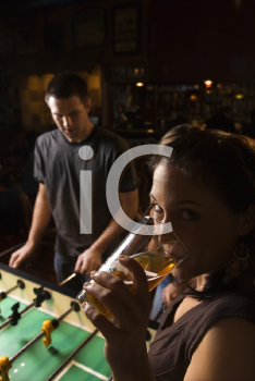 Royalty Free Photo of a Young Woman Drinking Beer While a Man Plays Foosball in a Pub
