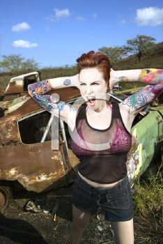 Royalty Free Photo of a Tattooed Woman Yelling and Covering Her Ears in a Junkyard