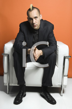 Royalty Free Photo of a Man in a Suit With a Mohawk Sitting in a Chair Against an Orange Background