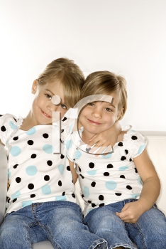 Royalty Free Photo of Twin Girls Sitting Together