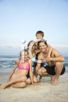 Royalty Free Photo of a Family of Four Posing Together on a Beach