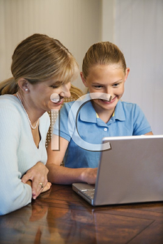 Royalty Free Photo of a Woman and Preteen Girl Using a Laptop Computer