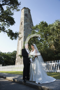 Royalty Free Photo of a Bride and Groom Standing Near a Lighthouse
