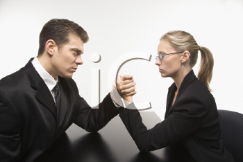 Royalty Free Photo of a Businessman and Businesswoman Arm Wrestling on a Table