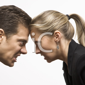 Royalty Free Photo of a Businessman and Businesswoman With Foreheads Together Wearing Hostile Expressions