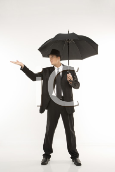 Royalty Free Photo of a Businessman Wearing a Fedora and Holding an Umbrella With Arm Outstretched