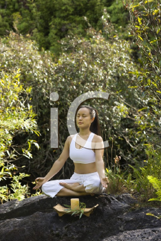 Royalty Free Photo of a Woman Sitting on a Boulder in the Forest Meditating With a Candle in Maui, Hawaii