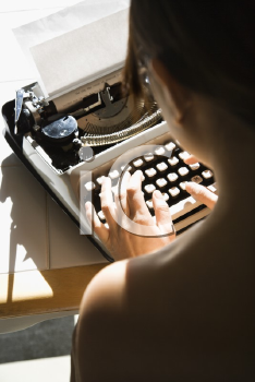 Royalty Free Photo of a Woman Sitting at a Kitchen Table Typing on a Typewriter