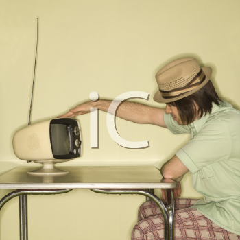 Royalty Free Photo of a Man Wearing a Hat Sitting at a 50's Retro Dinette Set Tapping an Old Television Set