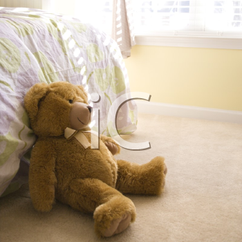 Royalty Free Photo of a Plush Brown Teddy Bear on a Bedroom Floor