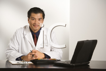 Royalty Free Photo of a Doctor Sitting at a Desk With a Laptop