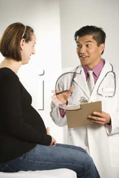 Royalty Free Photo of a Male Doctor Examining a Pregnant Female Patient