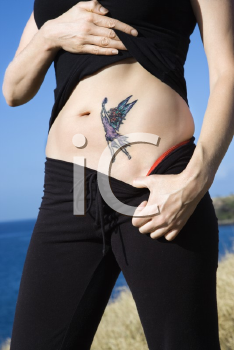 Royalty Free Photo of a Woman Exposing a Tattoo of a Fairy on Her Stomach
