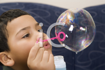 Royalty Free Photo of a Boy Blowing Large Soap Bubble