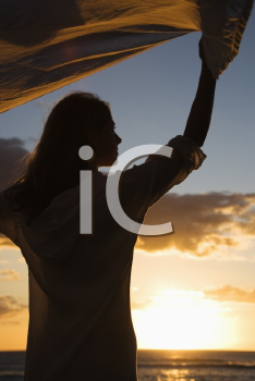 Royalty Free Photo of a Woman Holding Up Fabric in the Breeze Silhouetted By the Sunset