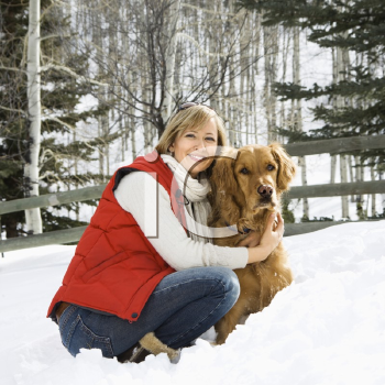 Royalty Free Photo of a Woman Hugging a Dog and Smiling in a Snow Covered Colorado Landscape