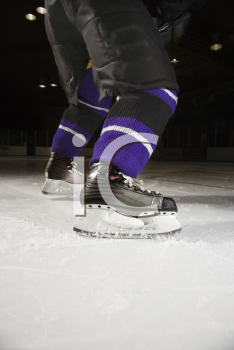 Royalty Free Photo of a Hockey Player's Legs and Skates on a Ice Rink