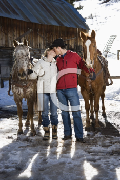 Royalty Free Photo of a Couple Kissing Holding Horses in Winter with a Stable in the Background