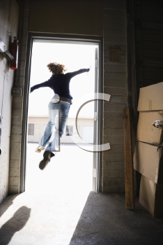 Royalty Free Photo of a Woman Running and Jumping Through an Open Door