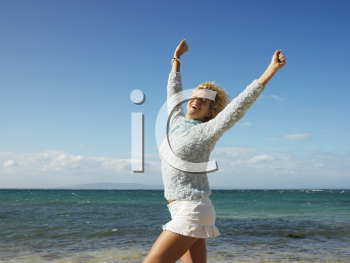 Royalty Free Photo of an Attractive Blond Woman Smiling With Arms Raised in the Air on Maui, Hawaii Beach