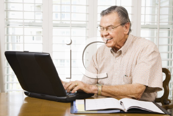 Royalty Free Photo of an Older Man Typing on a Laptop