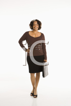 Full length portrait of businesswoman standing with hand on hip holding briefcase.
