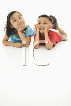 Asian brother and sister lying on floor with heads on hands.