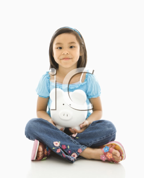 Asian girl sitting on floor holding piggybank.