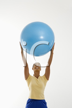 Royalty Free Photo of a Woman Standing and Holding an Exercise Ball Over Her Head