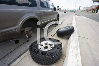 Royalty Free Photo of a Vehicle Broken Down Along the Roadside With a Damaged Tire Needing Replacement