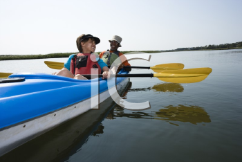 Royalty Free Photo of an African American Couple Sitting in a Kayak on a Lake Smiling and Laughing