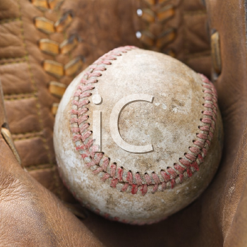 Royalty Free Photo of a Baseball Resting in a Baseball Glove