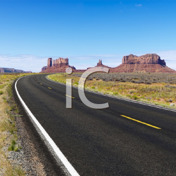 Royalty Free Photo of a Road in Scenic Desert Landscape With Mesa and Mountains