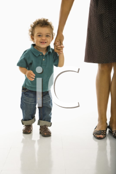 Royalty Free Photo of a Toddler Boy Holding onto His Mothers Hand Smiling