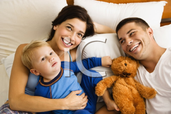 Royalty Free Photo of a Family Laying in Bed Smiling