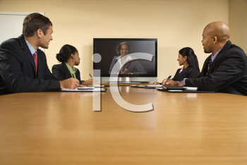 Royalty Free Photo of Businesspeople Sitting at a Conference Table Looking at a Flat Screen Display