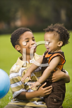 Royalty Free Photo of a Big Brother and Little Brother Playing With a Ball in a Park