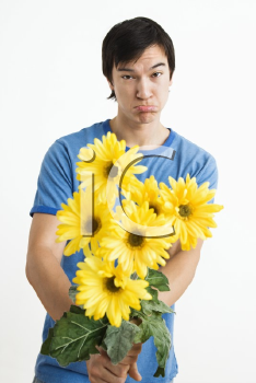 Royalty Free Photo of a Young Man Holding a Bouquet of Yellow Gerber Daisies While Pouting