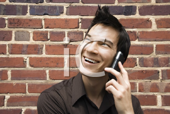 Smiling young Asian man next to brick wall talking on cell phone.