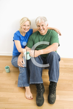 Royalty Free Photo of a Couple Sitting on the Floor Snuggling and Drinking Coffee