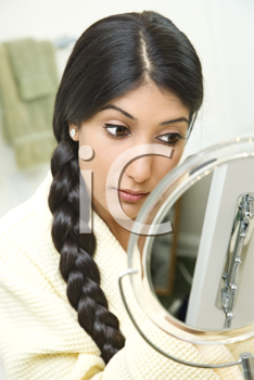 A young woman wearing a bathrobe is sitting in front of a mirror and applying makeup. Her long dark hair is braided and hanging over her shoulder. Vertical shot.