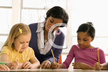 Teacher helping students with schoolwork in school classroom. Horizontally framed shot.