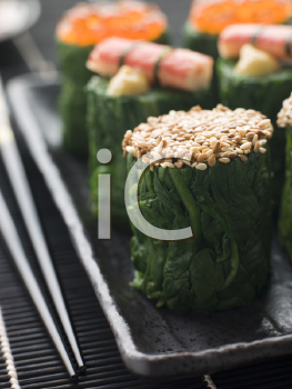 Royalty Free Photo of Rolled Spinach Three Ways-Snow Crab Toasted Sesame Seeds and Salmon Roe