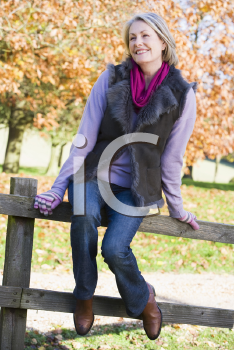 Royalty Free Photo of a Woman Sitting on a Fence