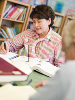 Royalty Free Photo of a Woman at a Table in a Library