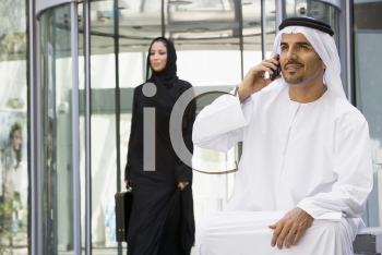 Royalty Free Photo of a Man With a Cellphone in a Lobby and a Woman Walking Behind