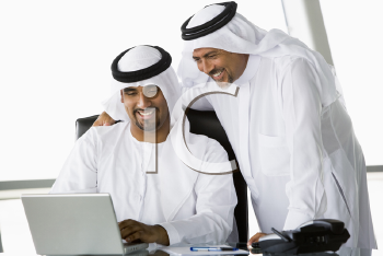 Royalty Free Photo of Two Eastern Men in an Office Looking at a Laptop